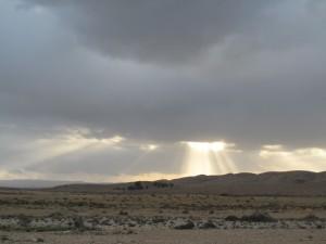 שמש בוקעת מעל ענני חורף במכתש הגדול